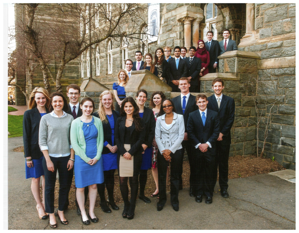 2013 Carroll Fellows, outside of Healy Hall, some standing on the ground, some standing on the steps, smiling for a formal photo.