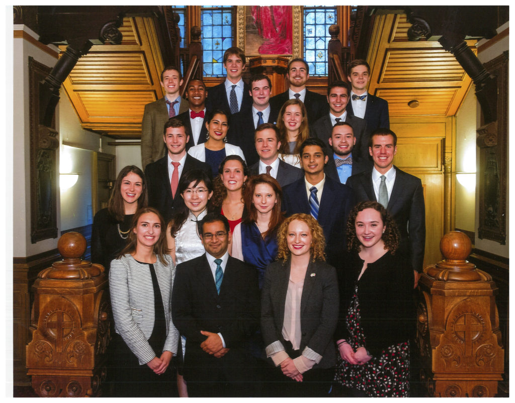 2014 Carroll Fellows, standing on the stairs in the lobby of Healy Hall, smiling for a formal photo.