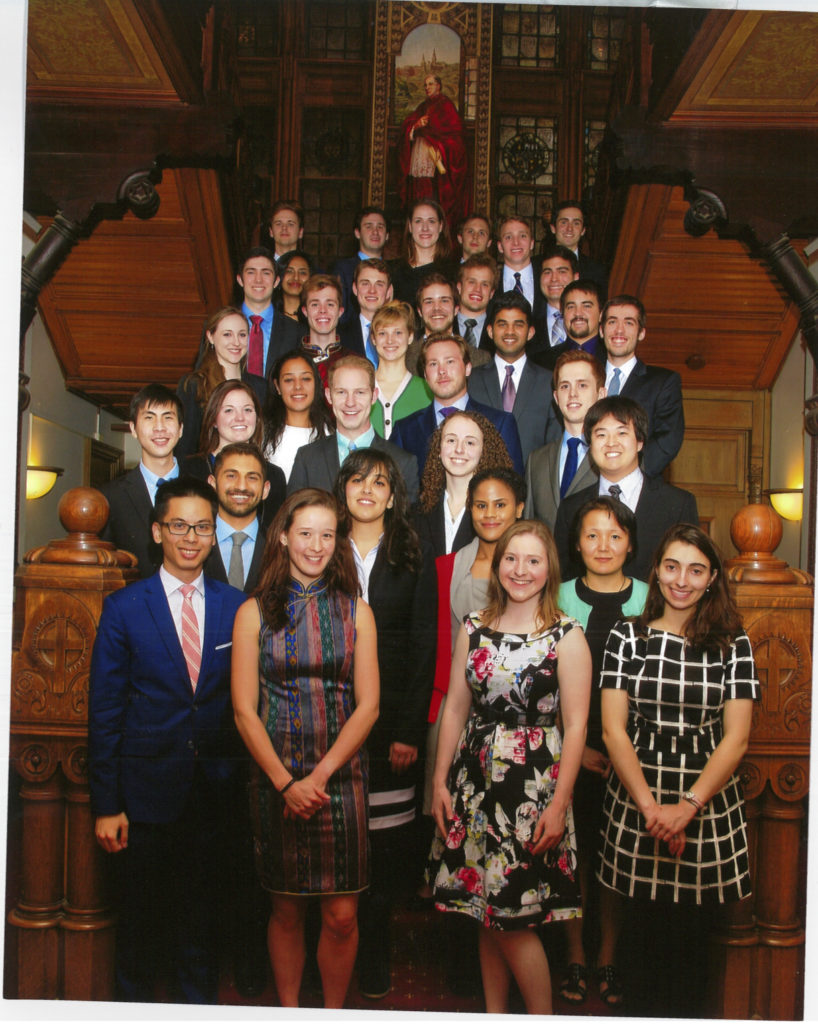2015 Carroll Fellows, standing on the stairs inside the lobby of Healy Hall, smiling for a formal photo.