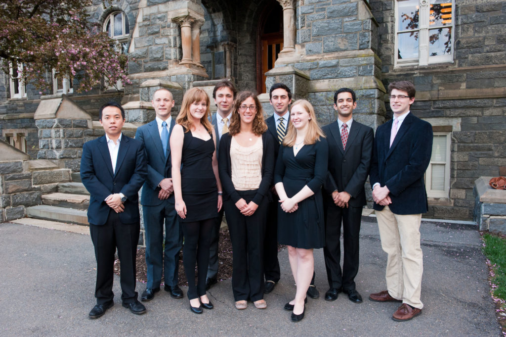 Carroll Fellows Class of 2011, standing in front of Healy Hall, wearing formal attire, smiling for the camera.