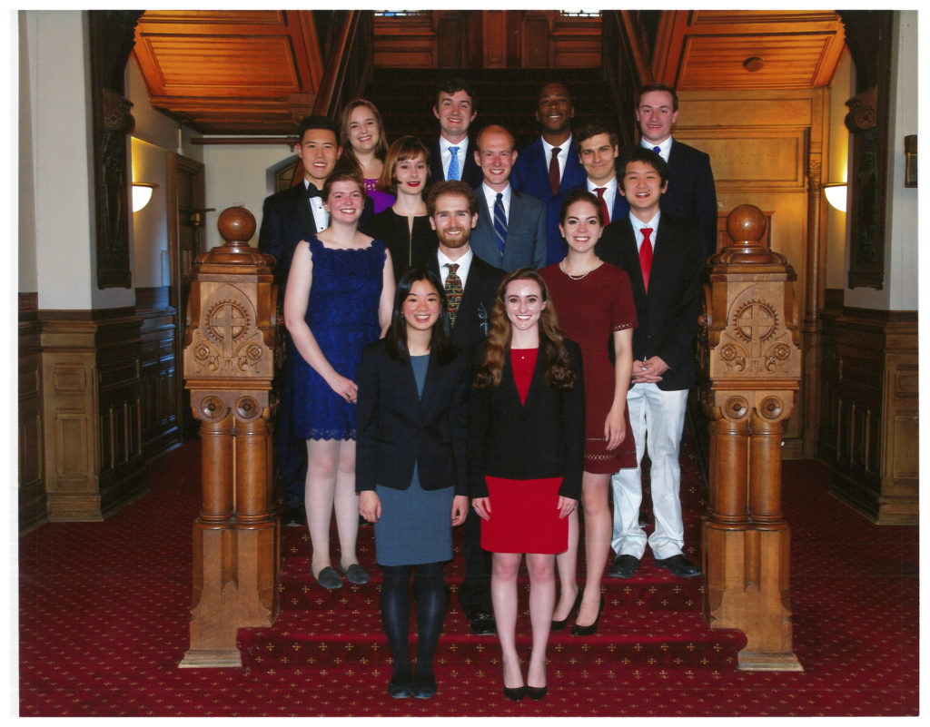 Carroll Fellows Class of 2017, standing inside the lobby of Healy Hall, wearing formal clothing, smiling for a photo.