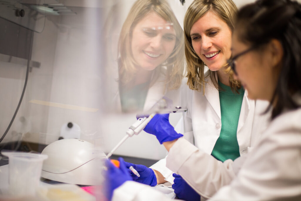 Two women, one student researcher and one faculty member, working in a research lab.